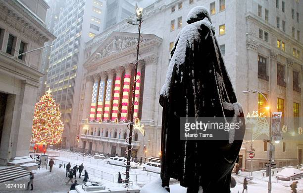 Statue of the first U.S. President George Washington is shown covered in snow in front of the New York Stock Exchange Christmas tree and holiday flag...