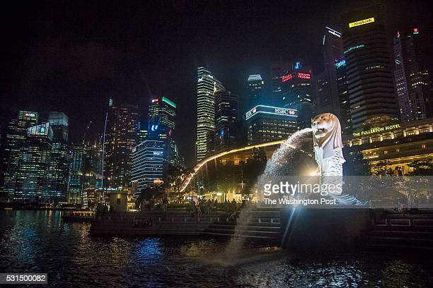 A statue of the Merlion a mythical creature with the body of a fish representing the roots of Singapore's fishing village origins and a lion's head...