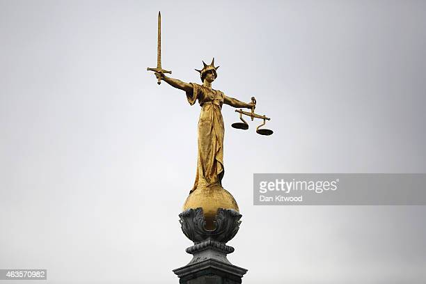 A statue of the scales of justice stands above the Old Bailey on February 16 2015 in London England