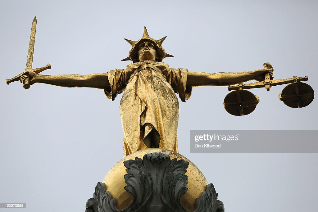 A statue of the scales of justice stands above the Old Bailey on February 16, 2015 in London, England.
