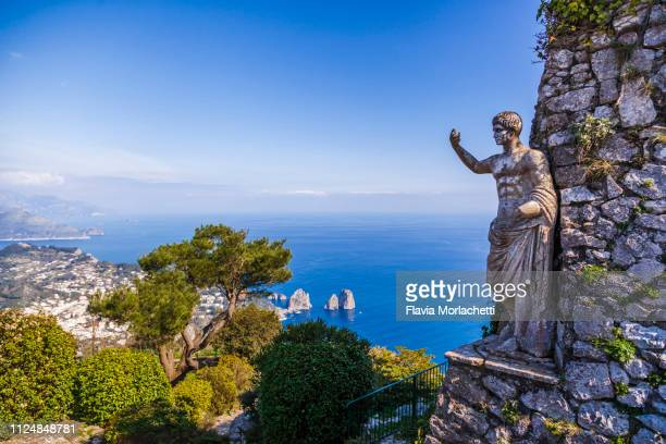 statue of tiberius in capri island with a view of faraglioni rocks, italy - mer tyrrhénienne photos et images de collection