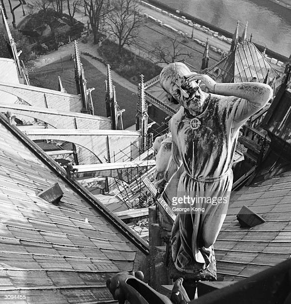 A statue of Violet le Duc French architect on the roof of Notre Dame de Paris He is dressed as an apostle and is looking up at his work the spire