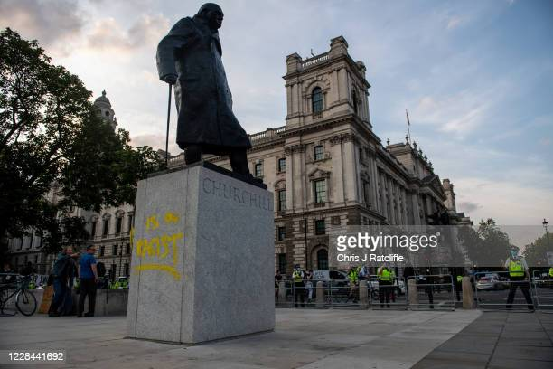 A statue of Winston Churchill is seen vandalised with spray paint as an Extinction Rebellion protest takes place in Parliament Square on September 10...