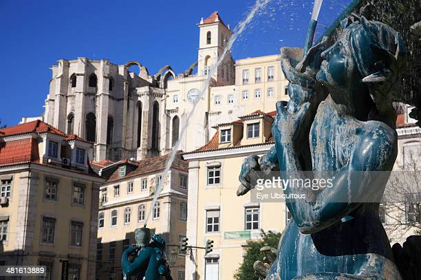 Statue on the fountain in Rossio Square with Carmo Convent in the background
