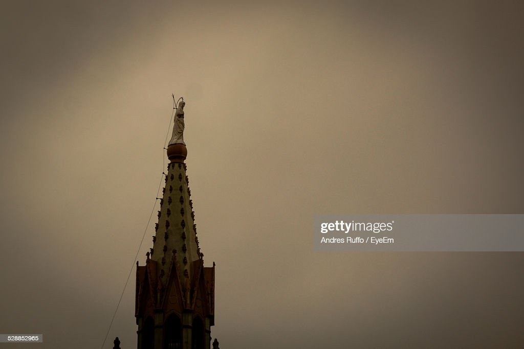 Statue On Top Of Steeple Against Sky At Dusk : Stock Photo