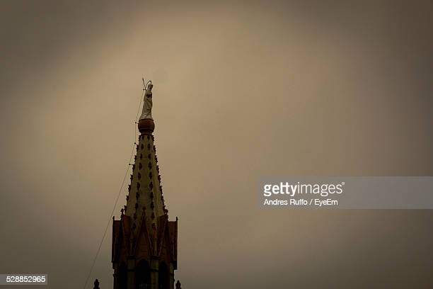 statue on top of steeple against sky at dusk - andres ruffo stock pictures, royalty-free photos & images