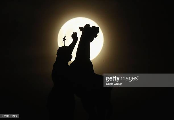 A statue on top of the Dom cathedral stands silhouetted against the socalled 'super moon' on November 14 2016 in Berlin Germany The 'super moon' is a...