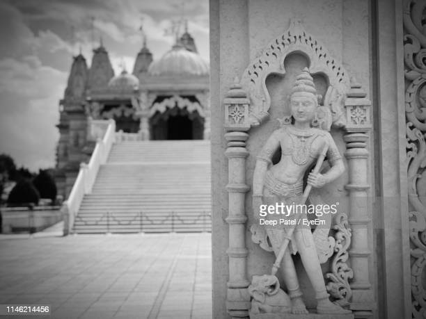 statue on wall at temple - cricklewood stock pictures, royalty-free photos & images