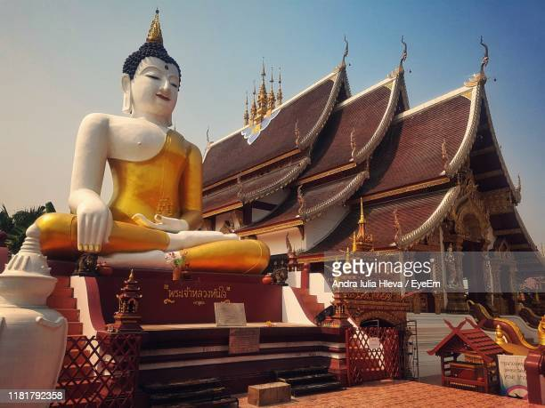 statue outside temple building against sky - wat pho stock pictures, royalty-free photos & images