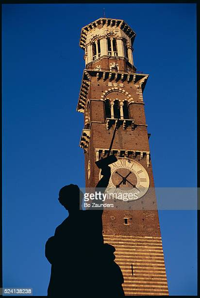 Statue Silhouette and Clock Tower
