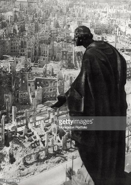 A statue sitting precariously in the middle of rubble is silhouetted against the skeletal walls of a neighbourhood wiped out by the Allied Forces...