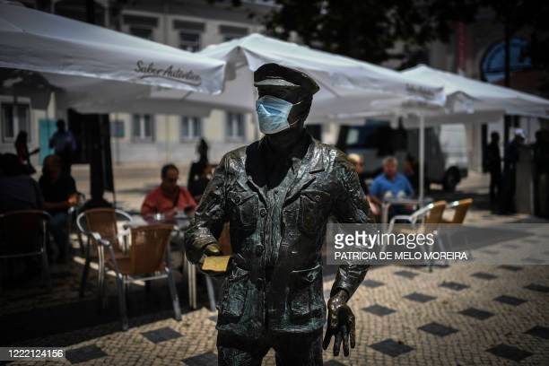 Statue wearing a face mask is pictured in downtown Lisbon on June 23, 2020. - Portugal's Prime Minister Antonio Costa said on June 22, 2020 that some...