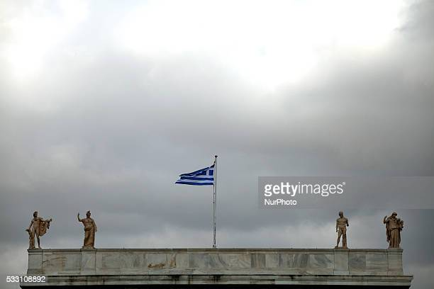 Statues and a greek flag on the top of National Archaeological Museum in Athens May 18 2016