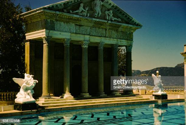 Statues and a Roman Temple facade sit at the edge of the Neptune Pool at Hearst Castle San Simeon California 1960