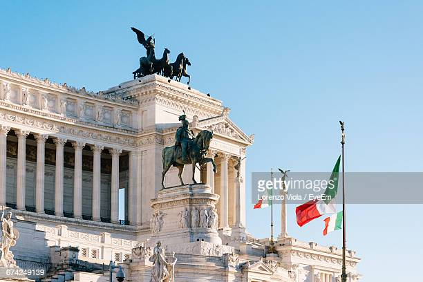 Statues And Italian Flags At Altare Della Patria Against Clear Sky
