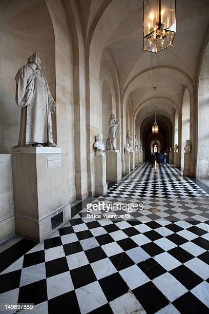 Statues of French kings on display in hallway of Chateau of Versailles.