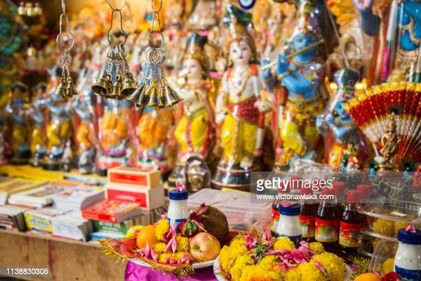statues of indian gods and flower sacrifices at dubai indian flower market - lord krishna stock photos and pictures