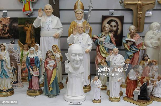 Statues of Pope Francis are displayed at a souvenir shop at Myeongdong Cathedral on August 13 2014 in Seoul South Korea Pope Francis will be visiting...