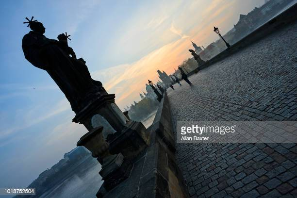 Statues of saints backlit on the iconic Charles Bridge