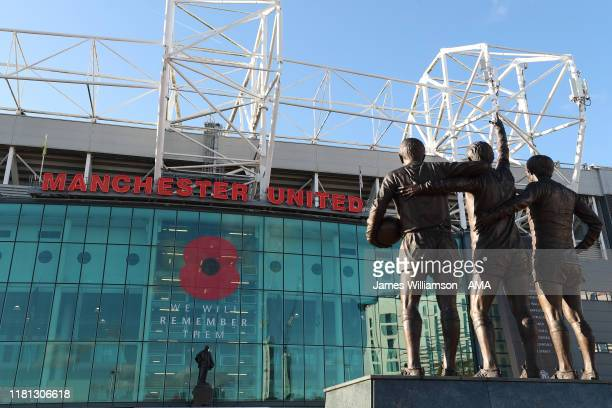 Statues of Sir Bobby Charlton George Best and Denis Law and a poppy on the Sir Matt Busby stand during the Premier League match between Manchester...