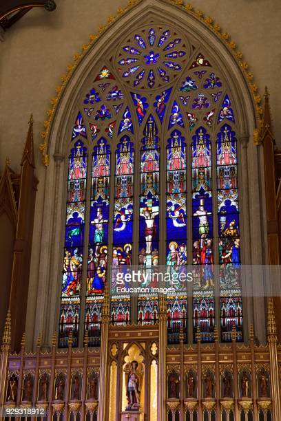 Statues of St Michael and 12 Apostles with Stained glass window of crucifixion in Cathedral Basilica Toronto