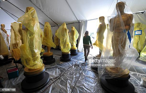 Statues of the Oscars remain in a tent before being transported to the red carpet and Dolby Theatre amid continuing preparations along Hollywood...