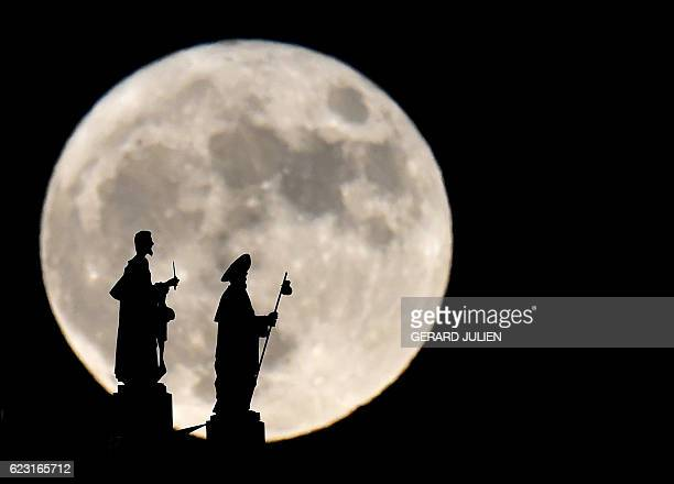 Statues on the Almudena cathedral are silhouetted against a Supermoon in Madrid on November 14 2016 The phenomenon happens when the moon is full at...
