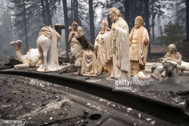 Statues stand on a burnedout vehicle in Paradise California US on Thursday Nov 15 2018 The number of acres burned in the blazes including the Hill...