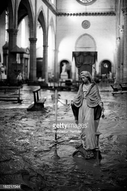 A statuette of Virgin Mary is incredibly left standing between the water and the mud inside the basilica of Santa Croce during the flood Florence 1966