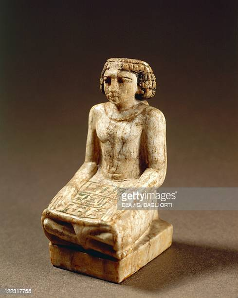 Statuette representing a scribe sitting crosslegged on the floor with hands on thighs and a papyrus scroll opened on the skirt