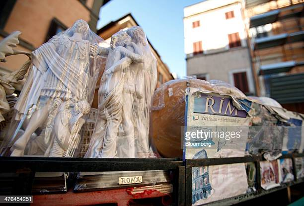 Statuettes sit on sale at a souvenir stall in Rome Italy on Monday March 3 2014 Italian Prime Minister Matteo Renzi is planning to demand stricter...