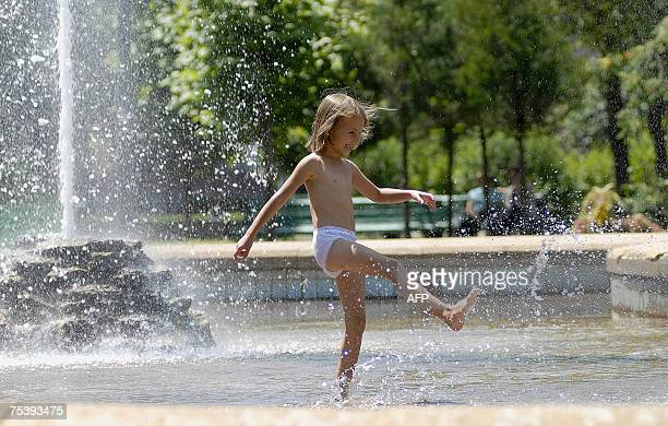 A little girl refreshes herself in a fountain in central Stavropol southern Russia 13 July 2007 as temperatures rise up to 35 degrees Celsius AFP...