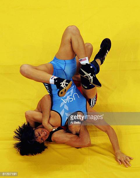 Stavroula Zygouri of Greece lifts Sara McMann of the USA during the women's Freestyle wrestling 63 kg qualification round on August 23, 2004 during...