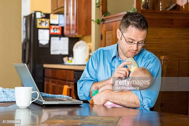 verbringen sie ihren aufenthalt im home father füttern baby bottle whle arbeiten - stay at home father stock-fotos und bilder