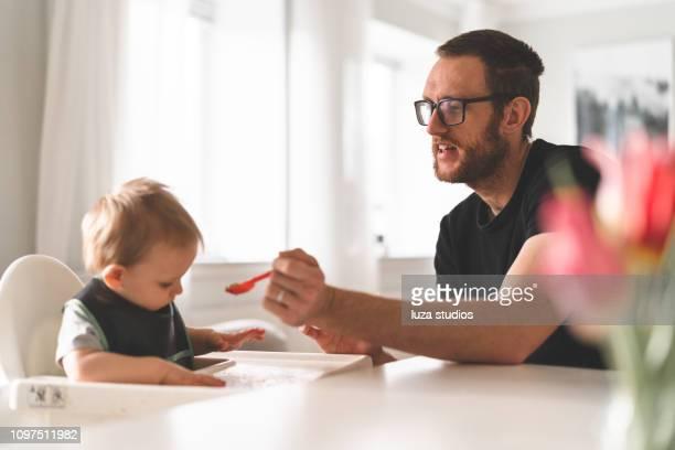 aufenthalt im hause vater füttert sein kleiner sohn - stay at home father stock-fotos und bilder