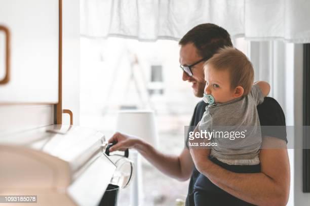 bleiben sie vater kaffeezubereitung mit seinem sohn am morgen zu hause - stay at home father stock-fotos und bilder