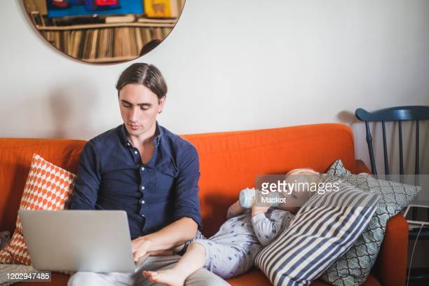 stay at home father using laptop while sitting by toddler son drinking milk from bottle on sofa in apartment - stay at home father stock-fotos und bilder