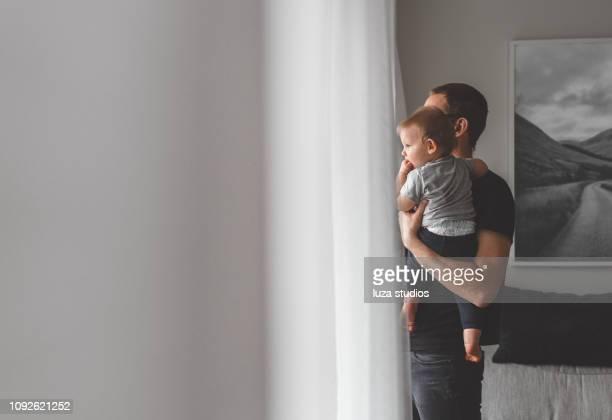 vater mit sohn baby zu hause bleiben - stay at home father stock-fotos und bilder