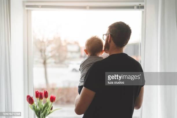 家に彼の赤ちゃんの息子を持つ父 - 主夫 ストックフォトと画像