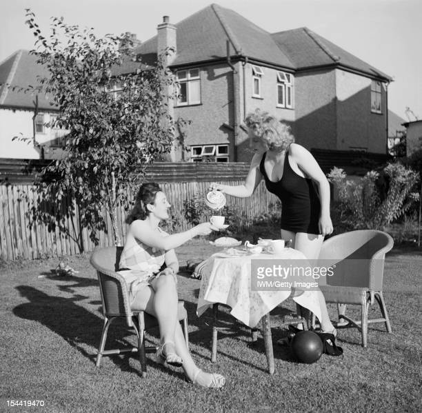 Entertainment And Relaxation In Wartime London England Peggy Franks pours tea for her friend Pinkie Barnes as they enjoy tea in the sunshine in the...