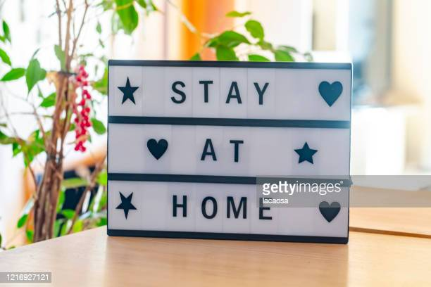 stay at home message in lightbox - stay at home order stock pictures, royalty-free photos & images