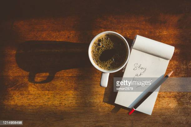 stay at home note on wooden textured table with a cup of black coffee - stay at home order stock pictures, royalty-free photos & images