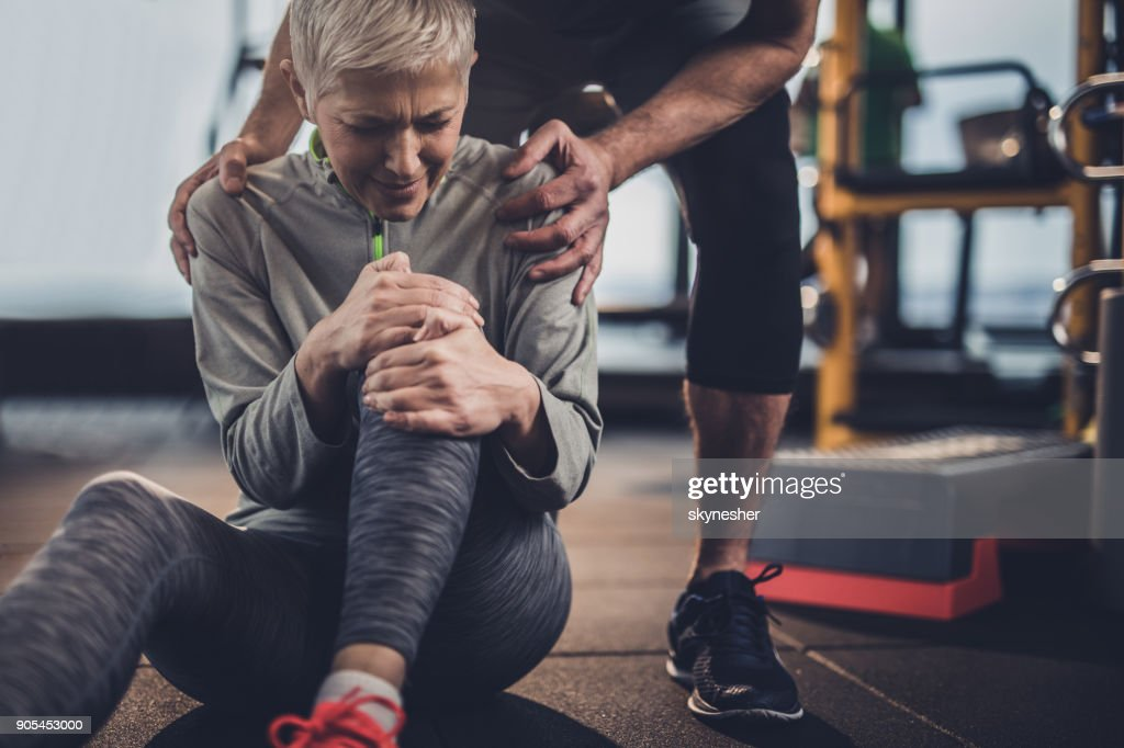 Stay down, I will help you with your injured knee! : Stock Photo