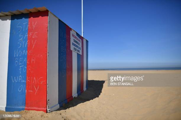 Stay Home slogans are seen on a beach hut on the deserted beach in Margate on April 11 2020 as warm weather tests the nationwide lockdown due to the...