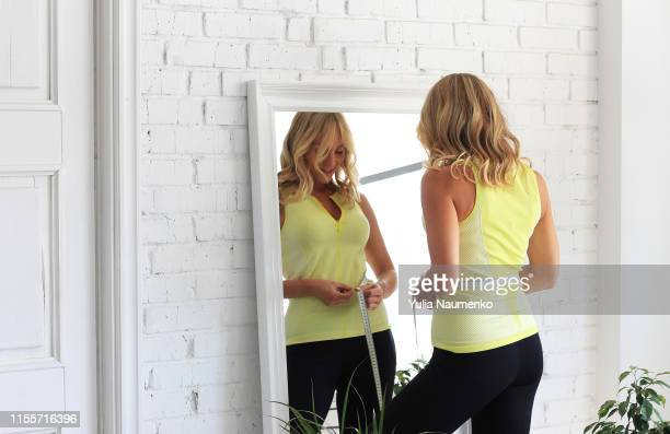 stay in shape. young woman with athletic body measures her waist with a measure type in front of a mirror. - big fat white women stockfoto's en -beelden