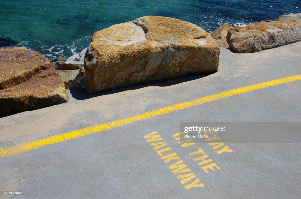 'Stay on the Walkway' sign stencilled in yellow paint on the concrete walkway of the Southern Break Wall at Coffs Harbour, New South Wales, Australia : Stock Photo