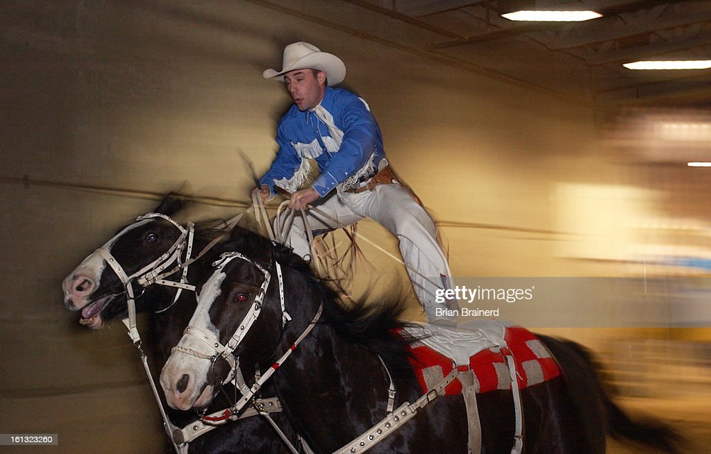 DENVER, CO, JAN 18, 2004 -- Stay with 'em! -- Trick rider, Shawn Brackett <cq>, 25, of Collinsville, OK, rides into the Great American Wild West Show through a portal in the National Western Events Center Sunday afternoon. Known as Roman Riding, he rides  : News Photo