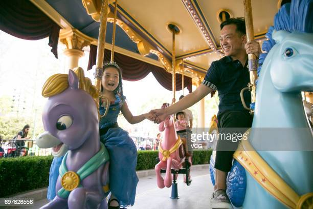 Stayathome father Qian Xiaofeng and his daughter Man Tou who wears the Princess Cinderella's dress made by Qian plays at Shanghai Disney Resort on...