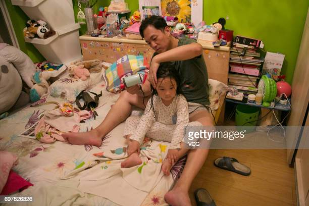 Stay-at-home father Qian Xiaofeng blows dry his daughter Man Tou's hair at home on June 15, 2017 in Shanghai, China. Stay-at-home father Qian...