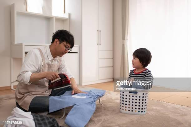 リビングルームでの在宅父のアイロン - 主夫 ストックフォトと画像